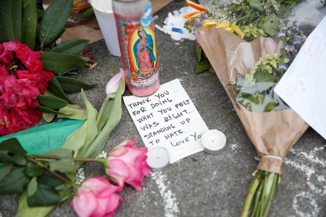 A candle with an image of Our Lady of Guadalupe is seen alongside a note and flowers at a makeshift memorial May 29 in Portland, Ore., for two men who were killed May 26 on a commuter train while they were trying to defend two young women from a man yelling epithets against them aboard a commuter train. Rick Best, a 53-year-old member of Christ the King Parish in Milwaukie, Ore., was one of the victims. (CNS/Reuters)