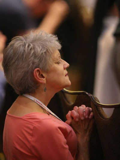 """A delegate prays during the closing Mass July 4 at the """"Convocation of Catholic Leaders: The Joy of the Gospel in America"""" in Orlando, Fla. (CNS/Bob Roller)"""