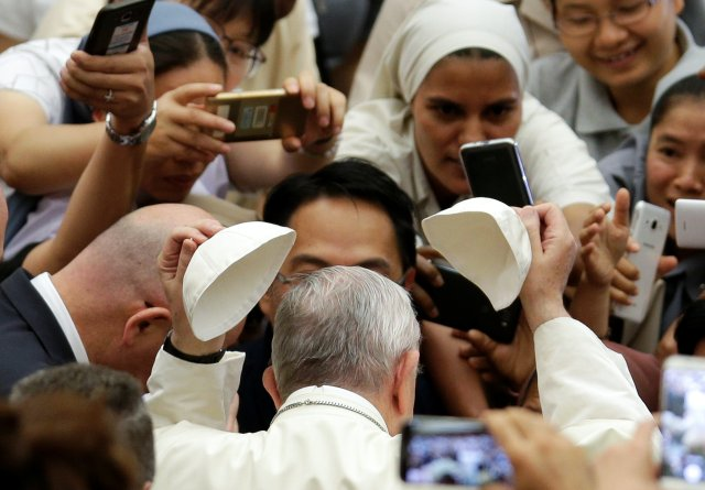 Pope Francis exchanges his zucchetto as he greets the crowd during his weekly audience in Paul VI hall at the Vatican Aug. 9 . (CNS/Reuters)
