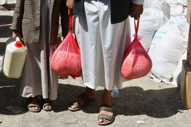 People receive food aid at a distribution center in Sanaa, Yemen, in this 2014 file photo. (CNS/EPA)