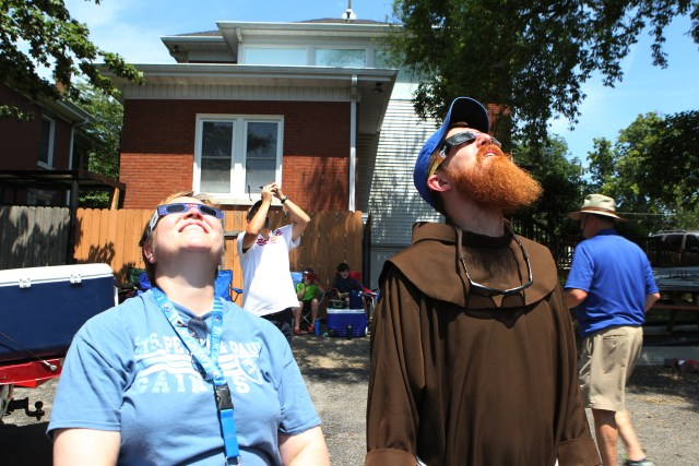 Jane Irwin, a science teacher at Sts. Peter and Paul School in Hopkinsville, Ky., and Franciscan Father Richard Goodin, vocation director for the Franciscans' St. John the Baptist Province in Cincinnati, view the solar eclipse moments before totality Aug. 21 in Hopkinsville. (CNS/Dennis Sadowski)