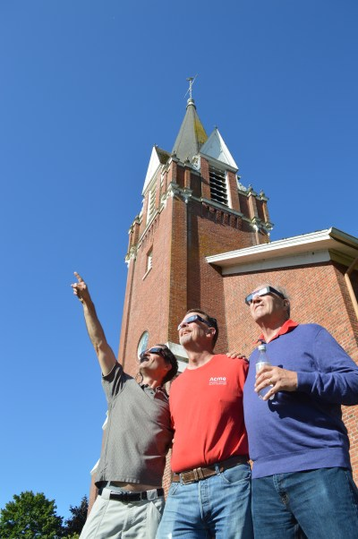 Pete Hamlin, Greg Clemmons and John Hedlund view the solar eclipse Aug. 21 in front of historic St. Paul Church in St. Paul, Ore. (CNS/Ed Langlois, Catholic Sentinel)