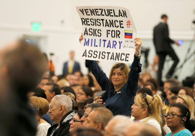 A woman displays a sign as U.S. Vice President Mike Pence speaks to a large crowd Aug. 23 at Our Lady of Guadalupe Church in Doral, Fla. (CNS/Reuters)