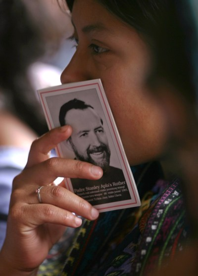 A woman holds a booklet with a picture of Father Stanley Rother, a priest of the Oklahoma City Archdiocese, during Mass in 2006 at a church in Santiago Atitlan, Guatemala. Father Rother will be beatified Sept. 23 in Oklahoma. (CNS/Reuters)