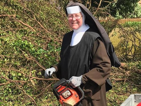 Carmelite Sister Margaret Ann, principal of Archbishop Coleman Carroll High School in Miami, holds the chainsaw she used to help clean up debris following Hurricane Irma. (CNS/courtesy Sister Margaret Ann)