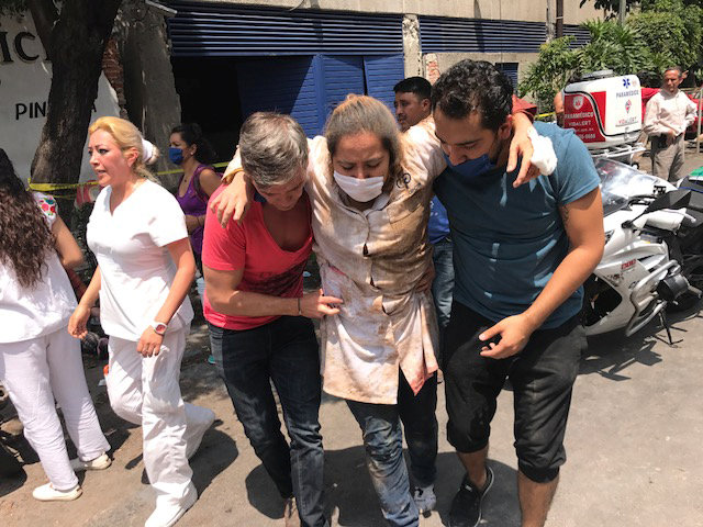 An injured woman is assisted in Mexico City Sept. 19 after a magnitude 7.1 earthquake hit to the southeast of the city, killing hundreds. (CNS/Reuters)