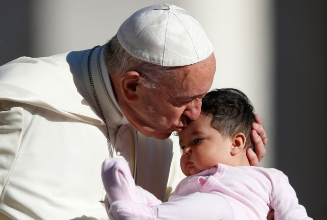 Pope Francis kisses a baby during his general audience in St. Peter's Square at the Vatican Sept. 20. (CNS/Paul Haring)