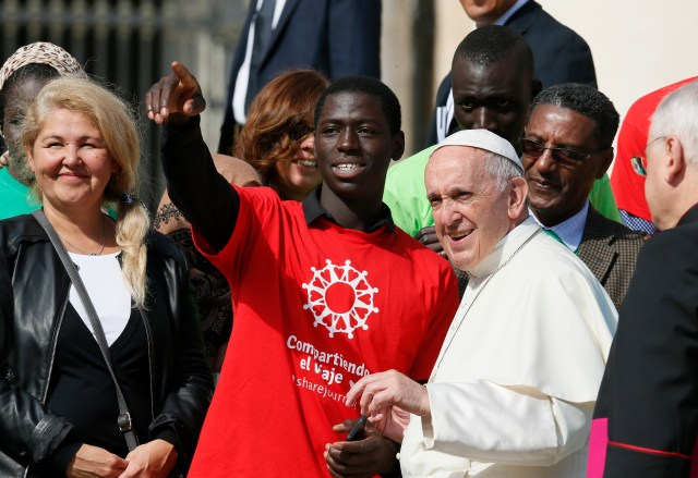 Pope Francis meets immigrants and representatives of Caritas Internationalis during his general audience in St. Peter's Square at the Vatican Sept. 27. He called on the people of the United States to welcome migrants during a live video conversation Oct. 26 with teens from around the world. (CNS/Paul Haring)