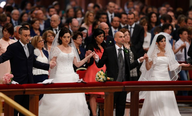 Newly married couples join hands to pray the Lord's Prayer during a Mass in St. Peter's Basilica at the Vatican. (CNS file/Paul Haring)
