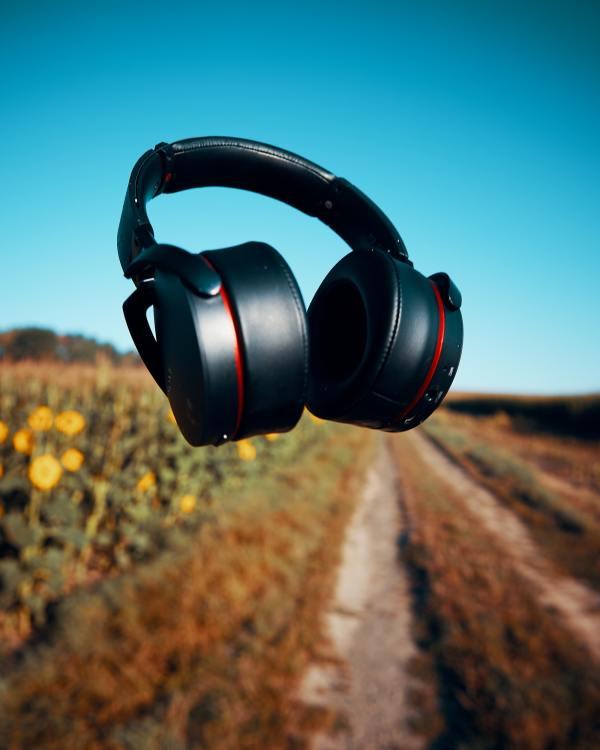Casque audio flottant dans les airs, avec un paysage de campagne en arrière plan