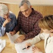 Senior couple meeting with an agent to go over estate planning.