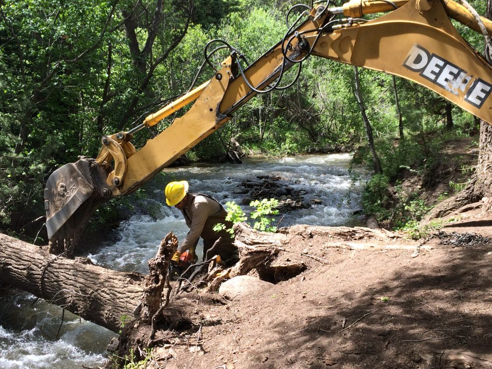 Man with an excavator behind him conducting river restoration