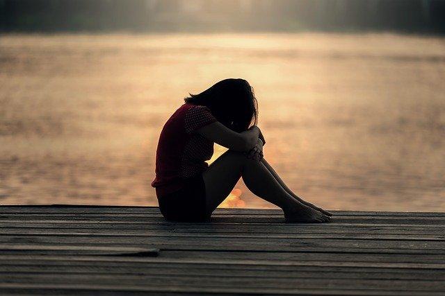 Wie du dir selbst Empathie geben kannst, wenn du verletzt wurdest - junge Frau sitzt in der Dämmerung auf einem Steg und legt den Kopf auf die Knie