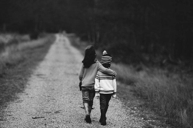Mädchen und Junge gehen Arm in Arm auf Feldweg entlang