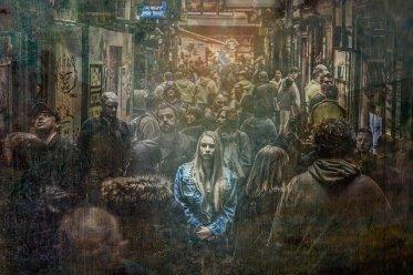 Gender Data Gap: eine bunte Frau in der Fußgängerzone inmitten dunkler Menschen, Stimmung trostlos