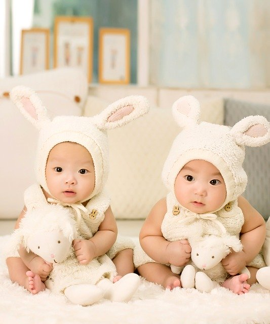 zwei Babyzwillinge im Hasenkostüm. Sie schauen sich sehr ähnlich.