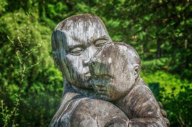 Holzskulptur: Mutter hat Kind über die Schulter, strahlt Geborgenheit, Trösten und Nähe aus
