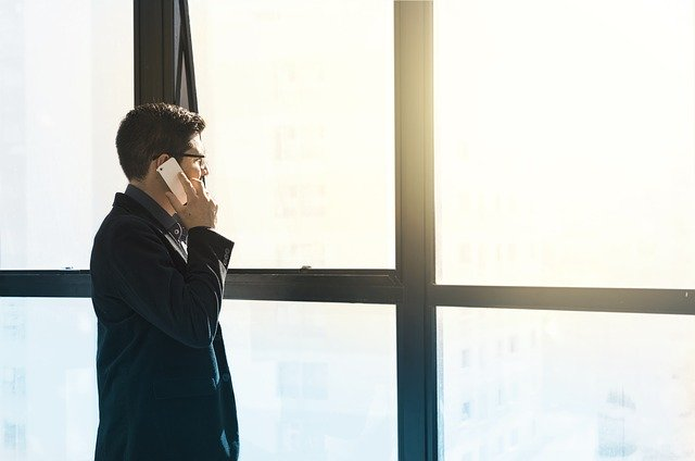 Kommunikationssperre Gordon: Geschäftsmann telefoniert mit Handy und blickt in die Ferne