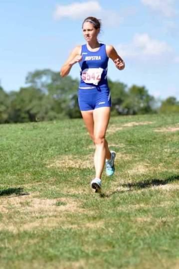 Girl running in grass wearing a Hofstra uniform.