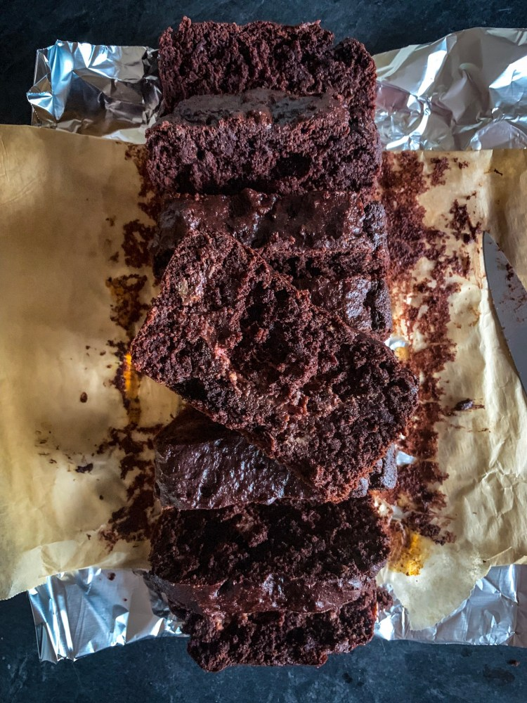 Breakfast recipe 3: chocolate banana bread, shown in 8 slices on top of parchment paper and aluminum foil.