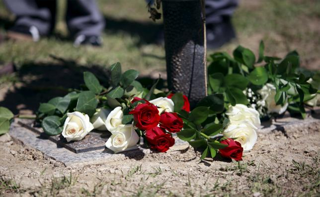 Roses are placed near the gravesite as relatives and friends gathered to remember Walter Scott, at Live Oak Memorial Gardens in Charleston, South Carolina, April 4, 2016. REUTERS/Randal Hill
