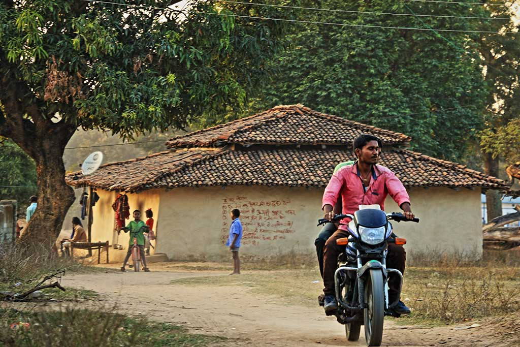 Man rides motorbike on a dirt road through village