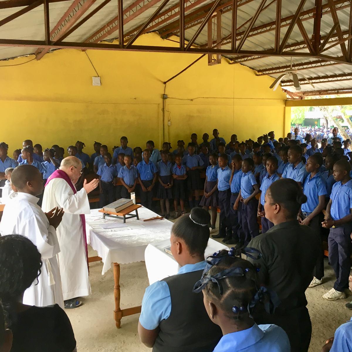 priest praying with children in kobonal