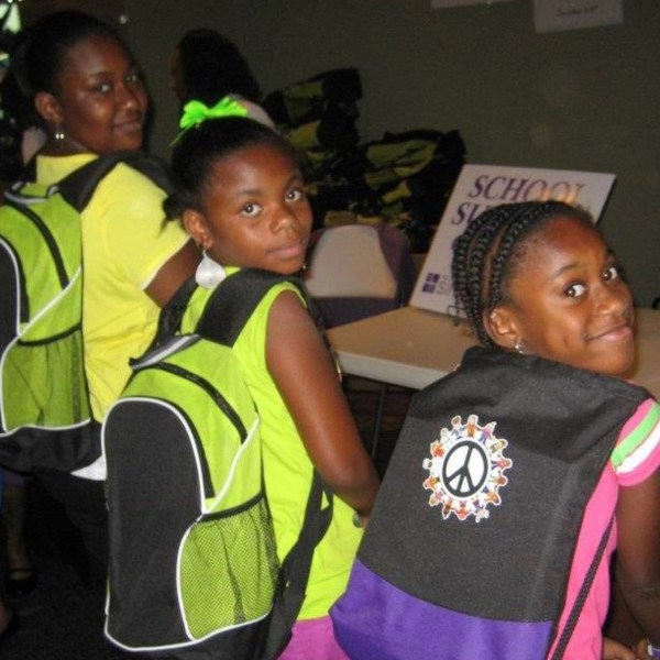 children smiling with new backpacks