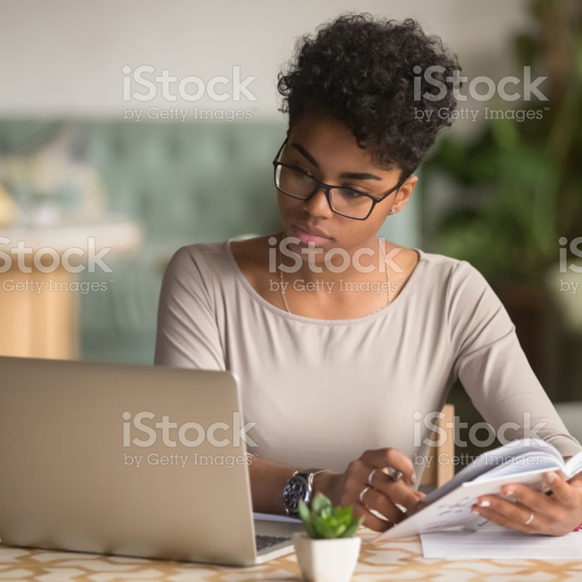 Focused young african american businesswoman or student looking at laptop holding book learning, serious black woman working or studying with computer