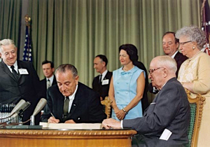 President Lyndon Johnson signs Social Security Act amendments creating Medicare as former President Harry Truman observes