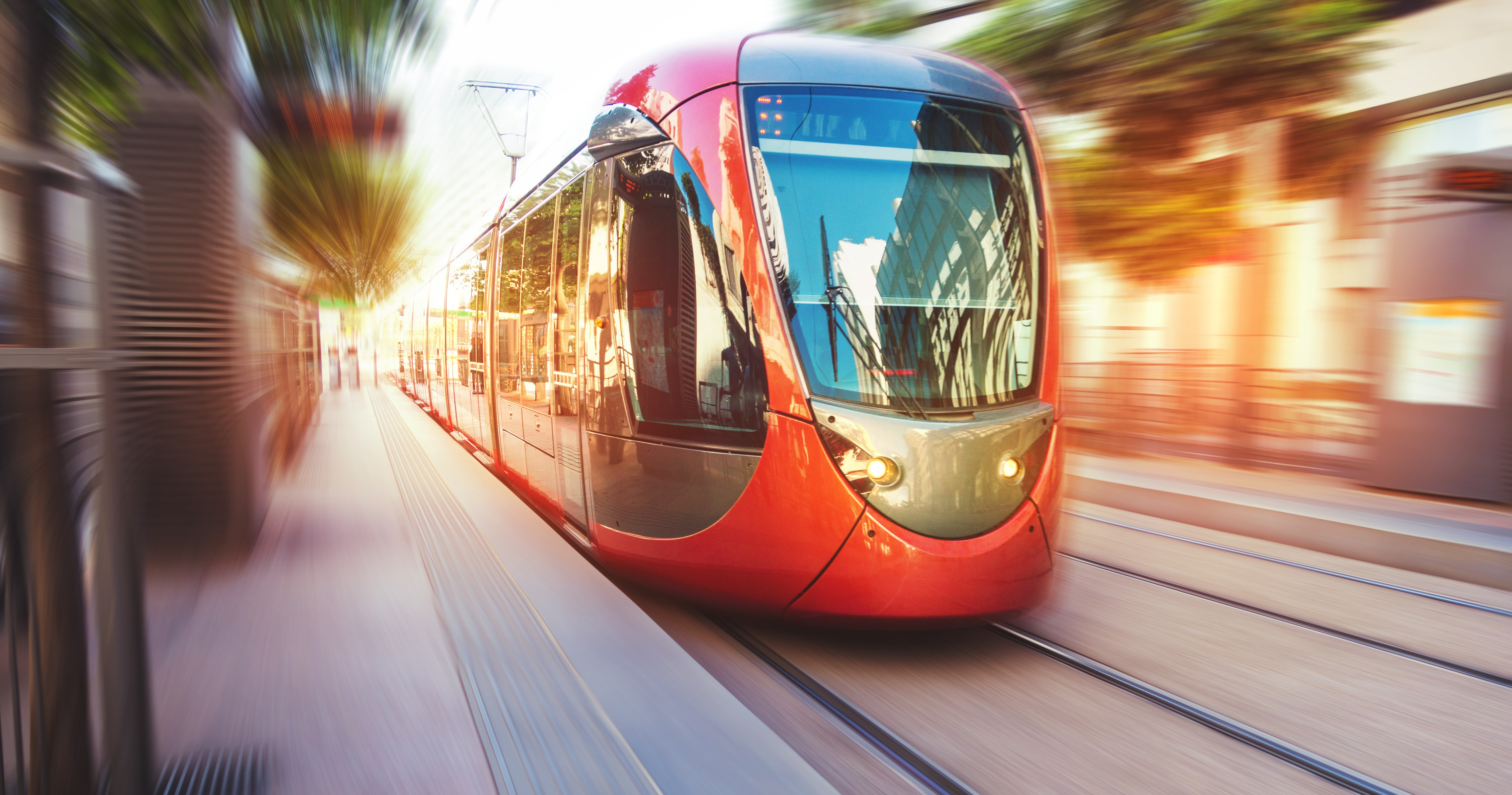 Modern red tram on city street