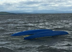 A submerged catamaran remains at the scene of a rescue in Lake Champlain, Vermont, June 8, 2016. A crew from Coast Guard Station Burlington pulled three people from the submerged hull after the 14-foot boat capsized in heavy winds about a mile from shore. (U.S. Coast Guard photo)