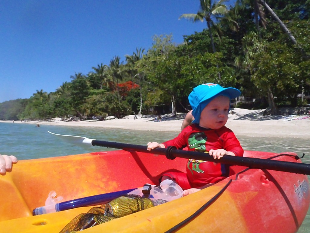 A baby in a kayak on an Australian beach