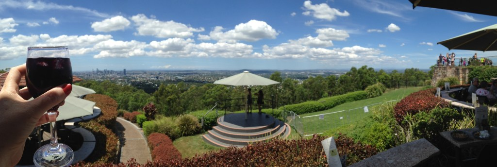 A panoramic view of Brisbane and surrounds taken from the top of Mount Coot-tha - wine glass in hand in shot.