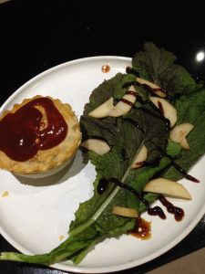 A pie and sauce served with home grown Asian greens, reduced balsamic sauce and sliced pear. I'm not sure what to call the dish!