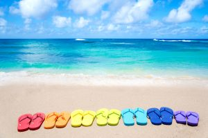 Colour flip flops on sandy beach by the ocean in sunny day