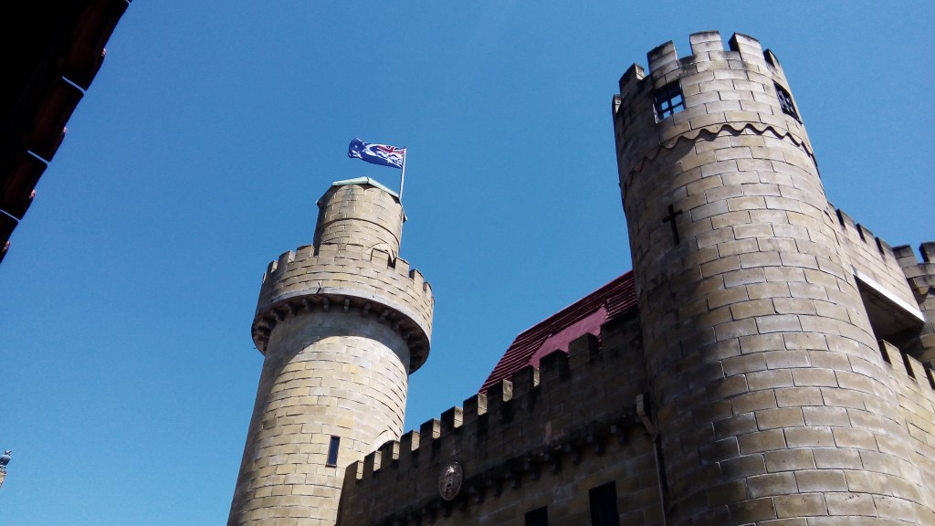 Turrets and castle walls against a clear blue sky with an Australian Flag at Sunshine Castle
