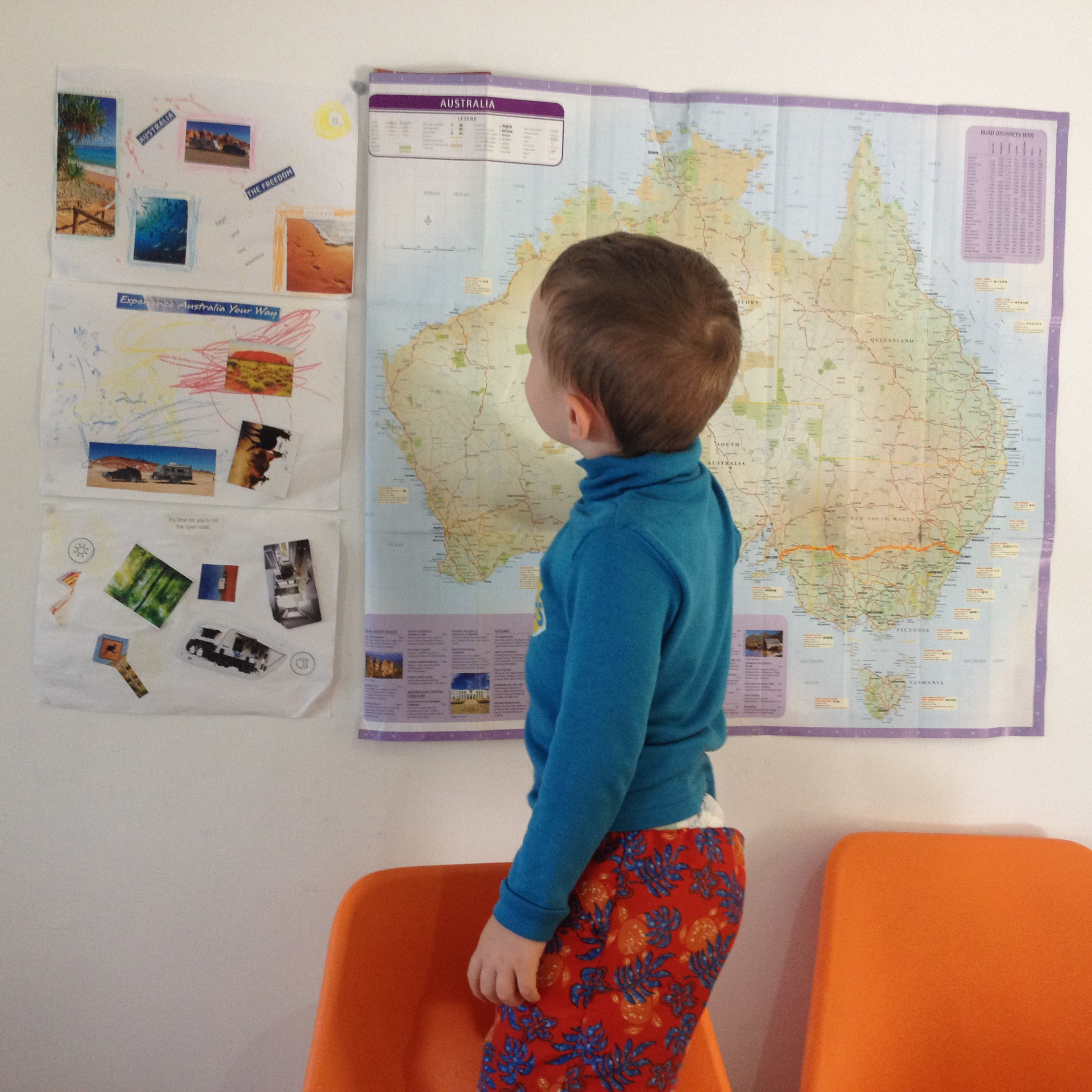 A boy looking at a map of Australia