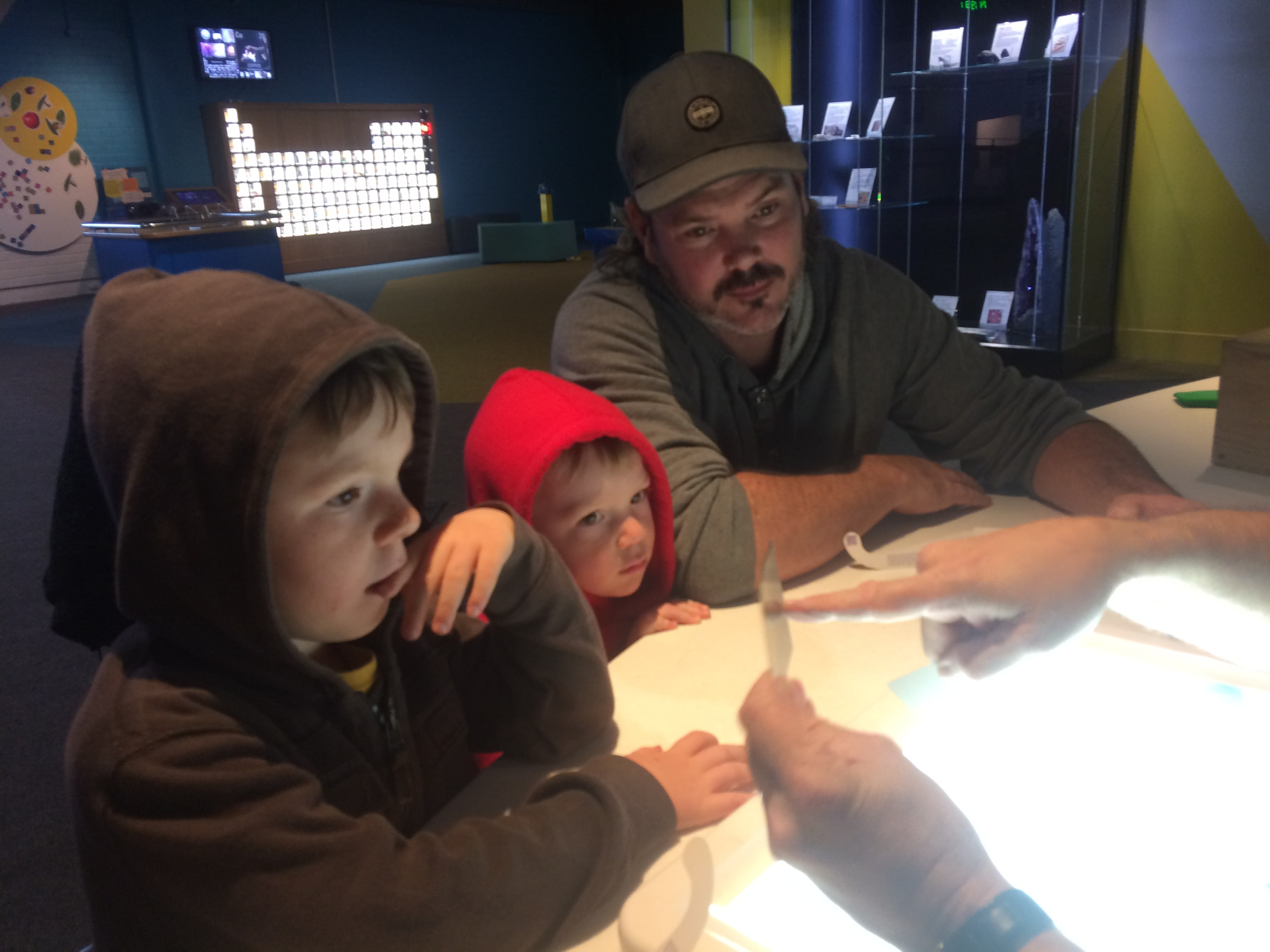 A dad and 2 sons enjoying a science experiment at Questacon in Canberra