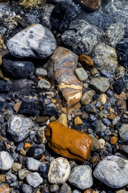 Orange, black, white and striped rocks match the strata on the cliff walls that surrounded the bowl stretching out from Bow Glacier Falls in Banff National Park. Dawn Page / CoastsideSlacking