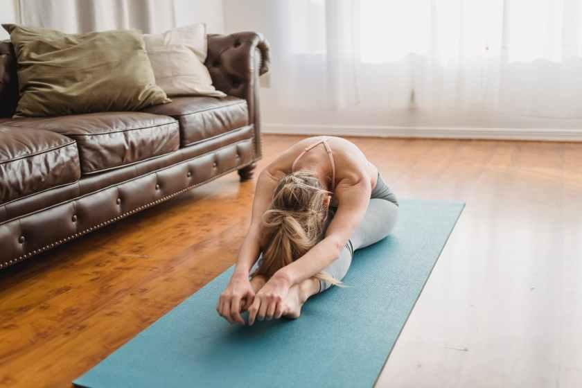 anonymous female yogi doing pascimottanasana stretching exercise on mat at home