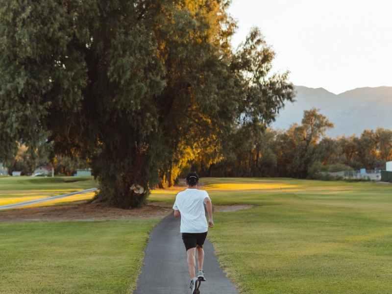unrecognizable woman jogging along footpath in park