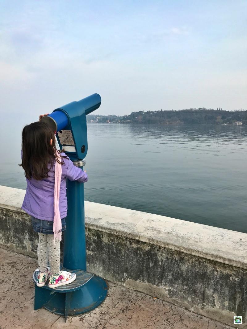 bambina che guarda attraverso il cannocchiale il lago di Garda
