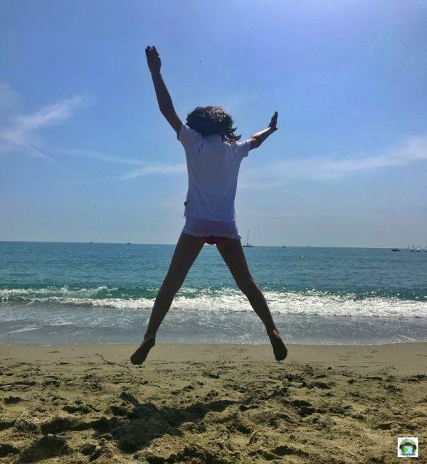bambina che salta in spiaggia a Varazze