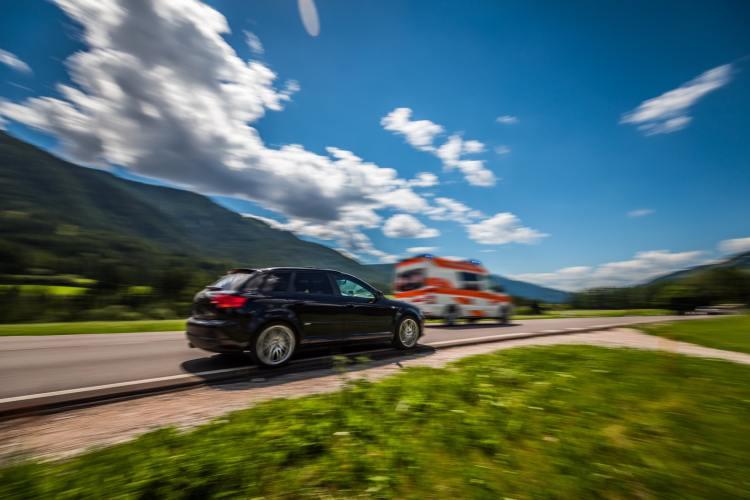 Car at high speed gives way to ambulance road