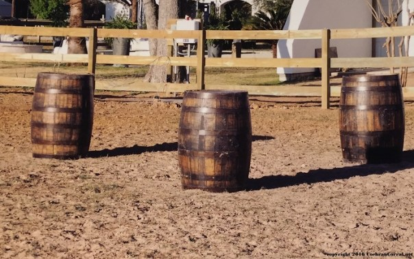 Three wine casks used as barrels for barrel racing in a dirt arena with a fence in the background.