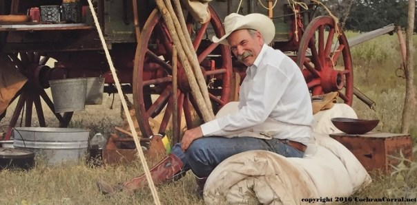 Glenn laughing on his bedroll next to the chuck wagon.