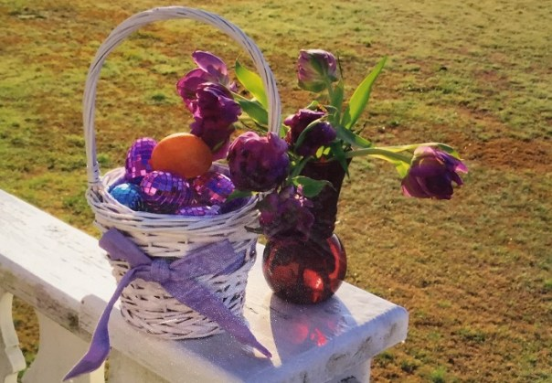 Easter Eggs in a white basket with a purple ribbon.