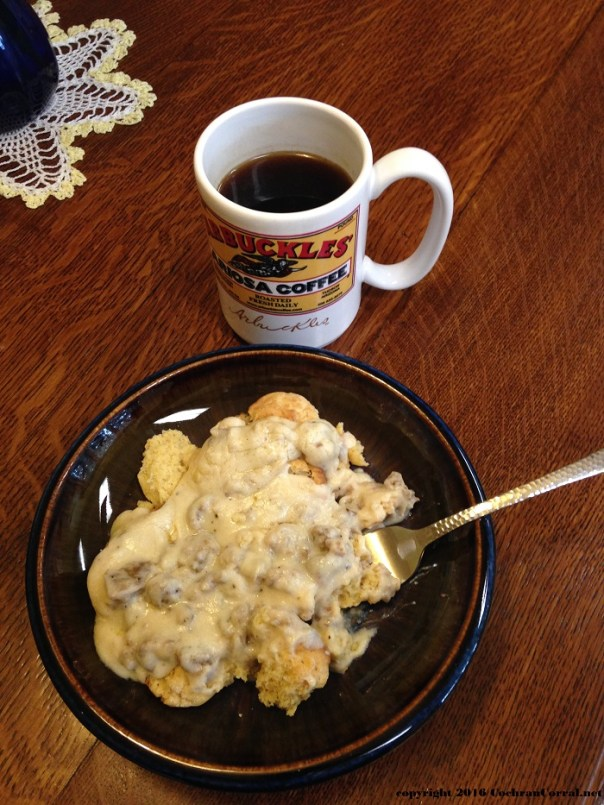 A cup of Arbuckles coffee and a bowl of biscuits and gravy!
