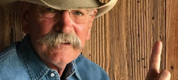 glenn holding up his index finger wearing an old felt cowboy hat